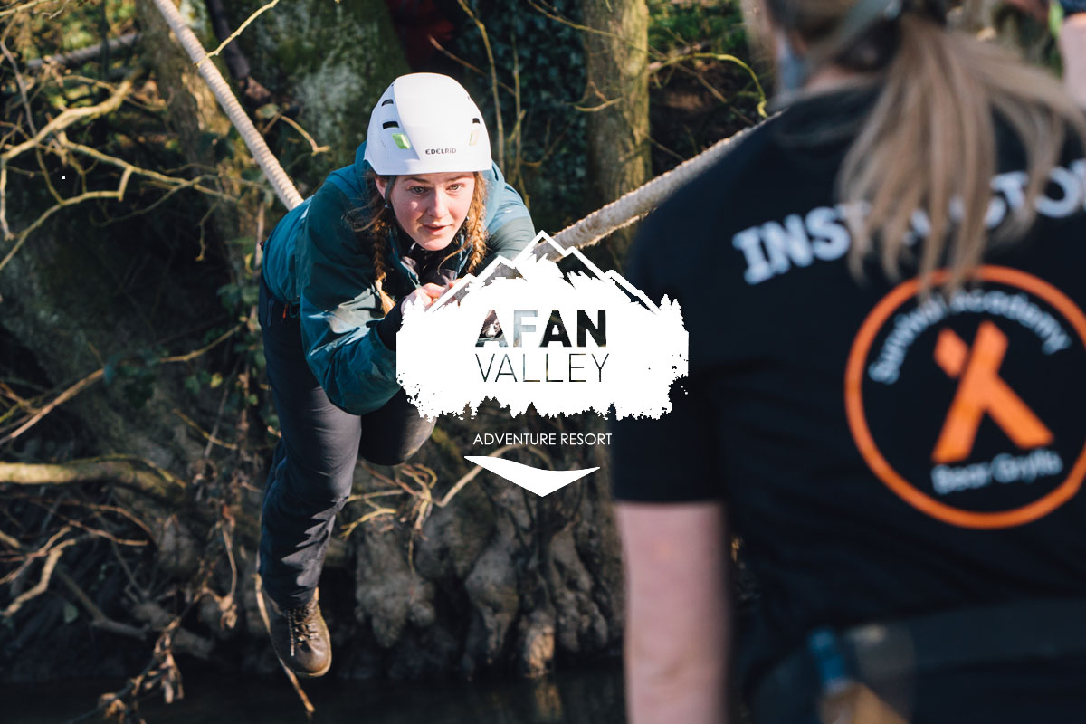 Girl climbing across rope as part of Bear Grylls Survival Academy at Afan Valley Adventure Resort